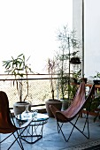 Leather butterfly chairs and coffee table on concrete balcony with potted plants and wire mesh balustrade