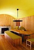 Vaulted ceiling painted lime green in interior with dining table and curved, wooden bench in front of modern, open fireplace