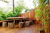 Wooden terrace with DIY tree-trunk stools and table in urban garden