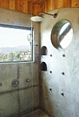 Shower in front of window with view in corner of bathroom with concrete wall panels and round recessed shelves