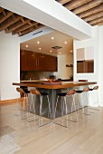 Designer bar stools at kitchen counter with wooden worksurface on stainless steel base in open-plan interior