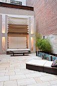 Modern, wicker sun loungers with pale cushions on stone-flagged floor of courtyard with awnings