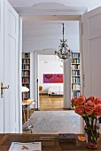 Vase of roses on desk in front of open double doors with view through library into living room of period apartment
