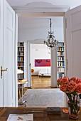 Rosenstrauss auf Schreibtisch vor offener Flügeltür und Blick durch Bibliothek ins Wohnzimmer in Altbauwohnung