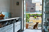 Kitchen with open doors leading to balcony; dog sitting in front of balustrade with window boxes