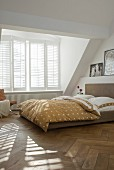 Sunny bedroom in natural shades with double bed in front of generous dormer window with interior, folding shutters