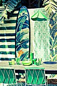 Lengths of wallpaper in various green patterns as background for outdoor dining area with matching accessories
