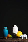 Arrangement of white head of Buddha, white hippo ornament, fruits and blue-glazed urn against dark background