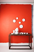 Stacks of white china crockery on wooden table below plates hung on red wall