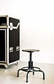 Black swivel stool and transport case on castors in front of patinated wall