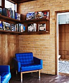 Armchair with royal blue cover in corner below wall-mounted shelves on brick wall