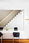 Large aperture in wall with integrated desk, laptops and modern chairs; view of staircase