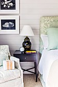 Black bedside cabinet with Chinese table lamp between armchair and bed against pale grey wooden wall