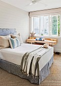 Scatter cushions on double bed with headboard against pale grey wooden wall next to wooden desk below window in simple bedroom