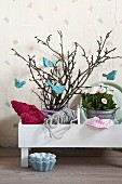 Romantic arrangement of pale blue, bird-shaped decorations hanging on spring branches and pink bellis in zinc pot in white planter
