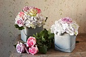Vintage ambiance with romantic arrangements of roses in small zinc buckets and roses on wooden table