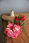 Zwei Blumensträusse in Papier gewickelt auf Holztisch liegend