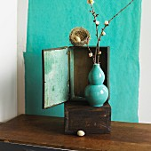 Bird's nest on wooden cabinet behind turquoise vase of flowering twigs