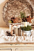 Tin cans of Christmas decorations on tray with metal dish leaning against wall in background