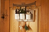 White tin cans with Christmas decorations hung on wooden interior door