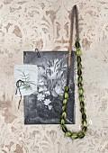 Grüne Kette aus Samenkapsen von der Nigellablume und Schwarzweissbild mit Blumenstrauss Motiv, an Wand mit verblichenem Ornamentmuster