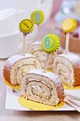 Zitronenrouladen-Schnitte mit Holzstäbchen und bedrucktem Kronkorken dekoriert auf weißer Porzellanplatte
