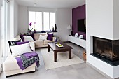 Bright modern interior with white corner sofa, dark wooden coffee table, white rug, purple accent wall and glass-fronted fireplace