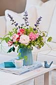 Blumenstrauss mit Rosen, Alchemilla, Katzenminze und Weinlaub in türkisfarbener Vase