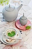 Teeservice mit Alchemilla-Deko und frischem Alchemillatee auf gemustertem Tischtuch