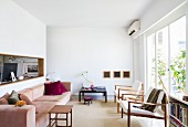 Minimalist, white interior with pastel couch and side table opposite armchairs and glass wall; hatch with view into study