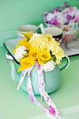 Yellow spring posy of tulips, carnations and narcissus in turquoise teapot