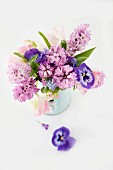 Spring posy of hyacinths, tulips and violas in pastel shades in pale blue enamel jug