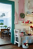 Romantically decorated sales room with fairy lights and country-house-style home accessories; view into cafe with nostalgic furnishings