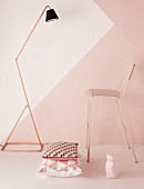Standard lamp with copper tube frame, bar stool and cushion with geometric patterns in front of wall in shades of pink
