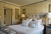 Schlafzimmer im klassisch englischen Stil mit elegant gestreifter Tapete, gepolstertem Kopfteil und Kissenparade auf Doppelbett