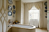 Collection of decorative plates above wood-clad bathtub with marble edge in stylish, English bathroom