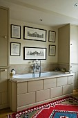 English bathroom in shades of beige with historical pictures, colourful Oriental rug and built-in bathtub