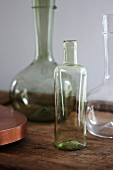 Three empty glass bottles on wooden table