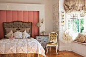 Romantic scatter cushions and ornate bedspread on antique bed against wall panel with dusky pink cover next to tutu on clothes hanger in bay window with ruched curtains