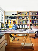 Woman sitting at large, corner desk in study with bookcase in background