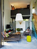Designer sofas in open-plan, double-height living area with staircase leading to gallery bridge