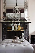 Fireplace decorated with Christmas stocking, garlands and glass reindeer below elegant mirror; silver tray on ottoman in foreground