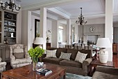 Upholstered furniture, dining area and kitchen in open-plan, elegant country-house interior with pillars