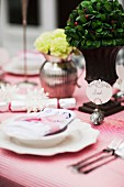 Table festively set with flowers, place card held by small metal bird and red and white striped tablecloth