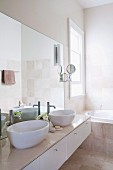 Bright modern bathroom with twin countertop basins on washstand with marble top
