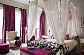 Four-poster bed decorated with fairy lights and purple textiles in elegant bedroom