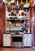 Pots, pans and old bundt cake tins hanging over kitchen counter with stainless steel cooker