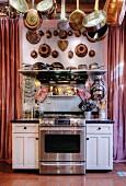 Küchenzeile mit Edelstahlherd, aufgehängten Töpfen, Pfannen und alten Napfkuchenformen