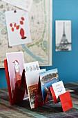 Various postcards in red-painted rack