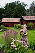 Woman cutting flowers in garden with simple wooden buildings in background